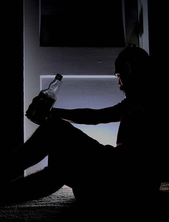 Alcoholic with bottle in hand crouched on floor.