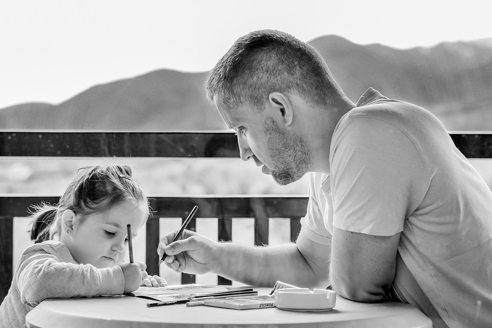 Dad and young daughter drawing together