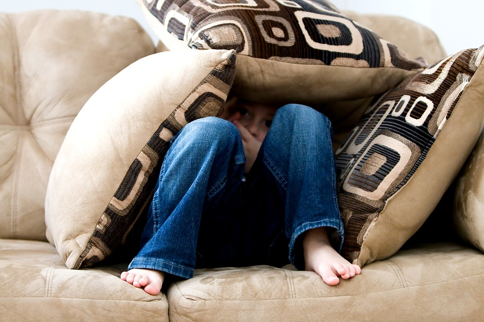 Diffcult child hiding under cushions